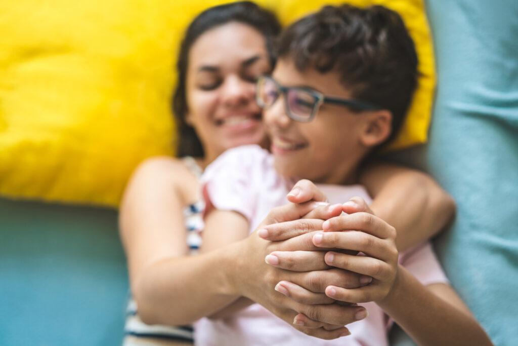 beneficio flexivel - Mãe feliz segurando o filho nos braços em cima da cama.